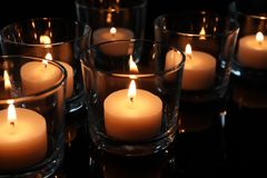 Velas de la cera que queman en la tabla en oscuridad fotografía de archivo libre de regalías