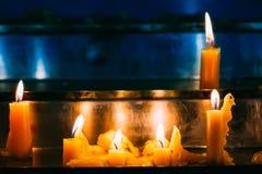 Velas de la fila en iglesia Llama ligera de la vela en la adoración Imagen de archivo