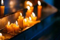Velas de la fila en iglesia Llama ligera de la vela en la adoración Imágenes de archivo libres de regalías