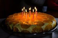 Velas de la iluminación en una torta de cumpleaños Fotos de archivo libres de regalías