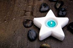 Velas de la turquesa en el candelero blanco de la estrella en la parte posterior gris de la pizarra foto de archivo
