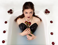 Velas de las rosas rojas del baño de agua de la leche de la muchacha fotografía de archivo