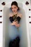Velas de las rosas rojas del baño de agua de la leche de la muchacha Fotografía de archivo libre de regalías