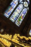 velas de oferecimento que queimam-se na catedral imagem de stock