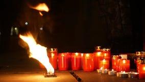 Velas de queimadura como um monumento à morte de um homem, chamas do vermelho impetuoso do fogo, um lugar no quadrado, um mágico vídeos de arquivo
