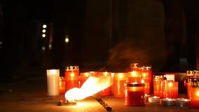 Velas de queimadura como um monumento à morte de um homem, chamas do vermelho impetuoso do fogo, um lugar no quadrado, um mágico filme
