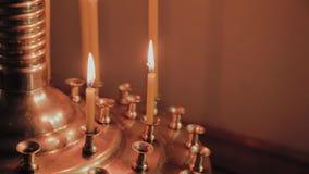 Velas de queimadura da igreja em um castiçal durante missas filme