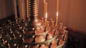 Velas de queimadura da igreja em um castiçal durante missas video estoque