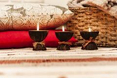Velas de queimadura do aroma dos termas no escudo do coco, nos descansos e na manta, fundo interior da casa acolhedor imagem de stock