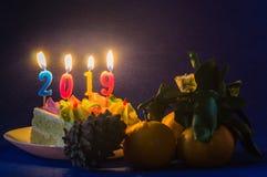 Velas de queimadura do feriado no bolo em uns pires brancos e em tangerinas com uma protuberância Ano novo 2019 foto de stock royalty free