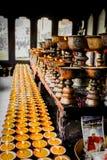 Velas de rogación y potes cepillados del metal en el monasterio de Zangdhopelri en Timbu, Bhután imagen de archivo