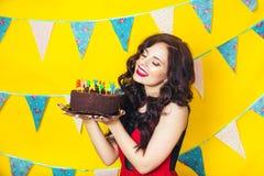 Velas de sopro da menina caucasiano bonita nela bolo Celebração e partido Tendo o divertimento Mulher bonita nova no vestido verm Foto de Stock