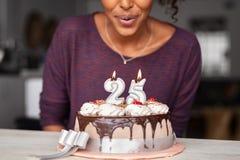 Velas de sopro do aniversário da mulher africana no bolo imagem de stock