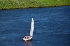 Velas de un yate de los deportes a lo largo del río por las orugas Imagen de archivo libre de regalías