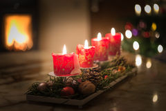 Velas del advenimiento con el árbol de navidad y el fuego ardiente de la chimenea Imagen de archivo libre de regalías
