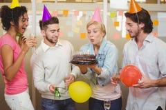Velas del cumpleaños de la empresaria que soplan en oficina Imágenes de archivo libres de regalías