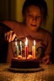 Velas del cumpleaños de la luz de la muchacha del niño Foto de archivo libre de regalías