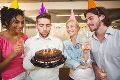 Velas del cumpleaños del hombre de negocios que soplan Imagenes de archivo