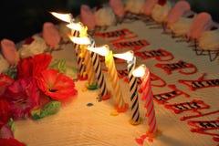 Velas del feliz cumpleaños en una torta Imagenes de archivo
