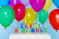 Velas del feliz cumpleaños en la torta con los globos Imagenes de archivo