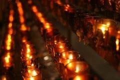 Velas del rezo en una iglesia Foto de archivo libre de regalías