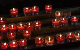 Velas devocionais vermelhas ardentes em pouca curva de vidro Imagem de Stock Royalty Free