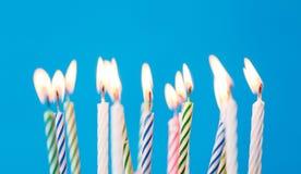Velas do aniversário que queimam-se sobre o fundo azul fotografia de stock royalty free