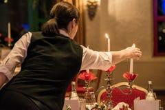 Velas do relâmpago da mulher no banquete com ajuste vermelho da tabela Imagens de Stock Royalty Free
