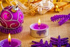 Velas e bola de incandescência do Natal na placa de madeira Fotografia de Stock Royalty Free