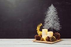 Velas e decorações do milho do pinho na tabela de madeira para o Natal Imagem de Stock