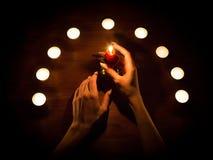 Velas e mãos fêmeas com pregos afiados Adivinhação e feitiçaria, baixa chave fotos de stock royalty free