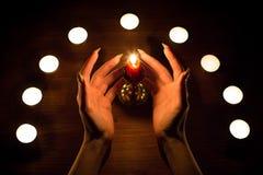 Velas e mãos fêmeas com pregos afiados Adivinhação e feitiçaria, baixa chave imagem de stock
