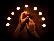 Velas e mãos fêmeas com pregos afiados Adivinhação e feitiçaria, baixa chave imagens de stock royalty free