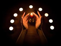 Velas e mãos fêmeas com pregos afiados Adivinhação e feitiçaria, baixa chave fotografia de stock