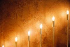 Velas eléctricas en palmatorias contra fondo del muro de cemento amarillo imágenes de archivo libres de regalías