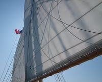 Velas em um veleiro com a bandeira americana dos EUA fotos de stock