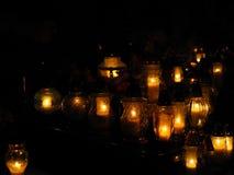 Velas en el sepulcro en el cementerio en la noche foto de archivo