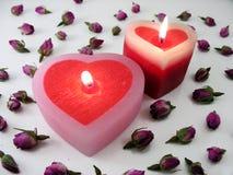 Velas en forma de corazón con los capullos de rosa Foto de archivo libre de regalías
