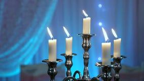 Velas en la palmatoria en la tabla de banquete Cinco velas almacen de video