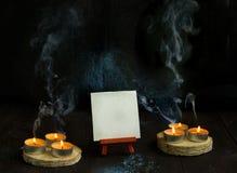 Velas en viejo fondo de madera con humo y el caballete Fotos de archivo libres de regalías