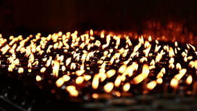 Velas encendidas alineadas en fila y resplandor en el espacio oscuro almacen de metraje de vídeo