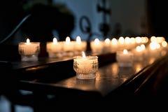Velas encendidas en la iglesia en la tabla en el fondo de la reflexión de la cruz Imágenes de archivo libres de regalías