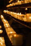 Velas encendidas que se colocan en filas Imagen de archivo libre de regalías