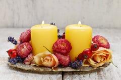 Velas entre las flores - decoración de la tabla Imágenes de archivo libres de regalías