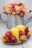 Velas entre las flores - decoración de la tabla Fotos de archivo