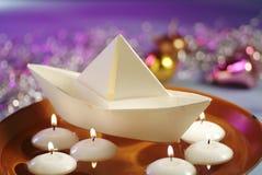 Velas flotantes y barco de papel Foto de archivo libre de regalías