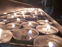 Velas iluminadas em uma igreja Imagens de Stock