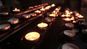 Velas iluminadas no templo no crep?sculo Velas ardentes da igreja filme