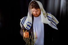 Velas judaicas da celebração do Hanukkah que queimam-se no menorah, homem no fundo imagens de stock