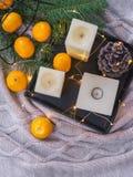 Velas, mandarinas anaranjadas, cono del pino en la bandeja negra y luces de hadas acogedoras en backgroundand de la tela escocesa imagenes de archivo